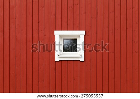 Red wooden wall with small window in white frame, typically Scandinavian living house architecture fragment