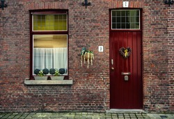 Red wooden window with white curtains and door with heart-shaped wreath. Brick house in Bruges, Belgium