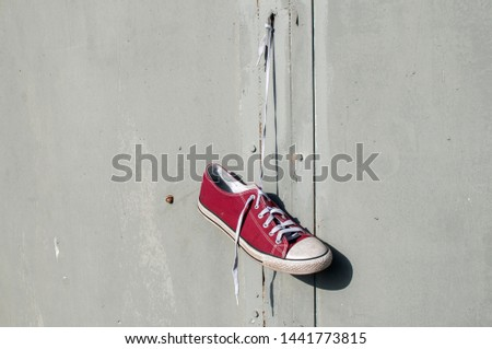 Red worn out vintage old canvas sneaker hanging on his laced ties #1441773815