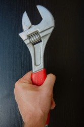 Red wrench on a black background. Male hand and red tool. Plumbing repair background.