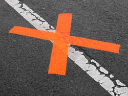 red x on white line asphalt no parking