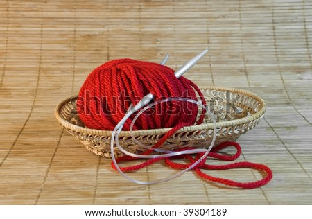 red yarn ball and needles in the basket