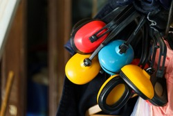 Red yellow and blue ear muffs hanging in storage basement or room in day close up ear sound noise protection