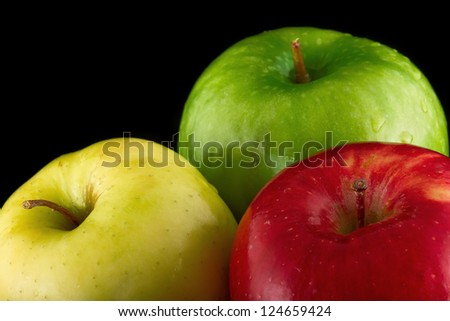 Red, Yellow and Green Apple on a black background