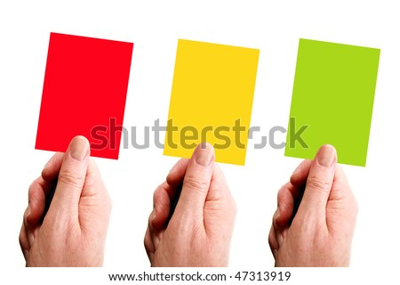 Red, yellow and green cards held by hand over a white background