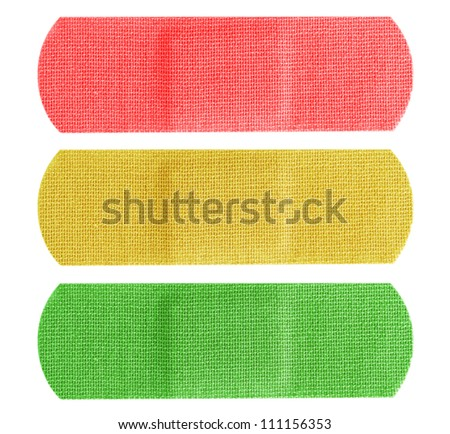 Red, yellow and green color bandaids or bandages isolated on white background.