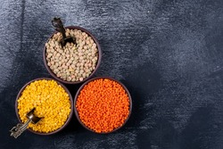 Red, yellow and green lentils in a brown bowls on a black stone background. top view. copy space for text