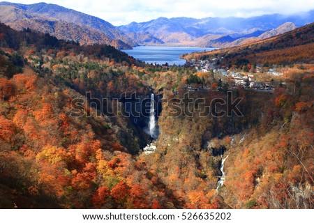 Red, yellow, and orange autumn foliage on mountain with a blue lake (Lake Chuzenji) and a great falls (Kegon Falls). Photoed at Akechidaira observatory, Nikko, Tochigi, Japan.