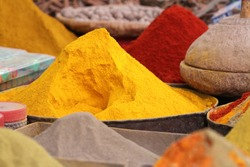 Red, yellow and orange spices in a pile in a farmers market