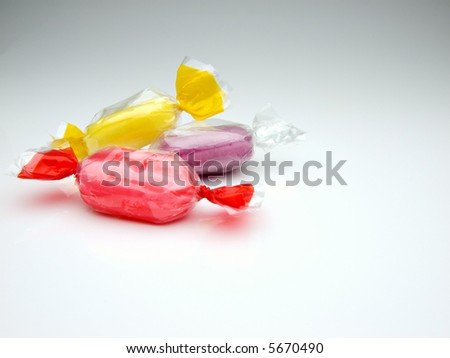 red, yellow and purple candies wrapped in cellophane foil on white surface