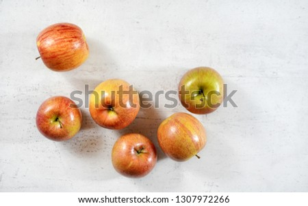 Red / yellow apples (kiku variety) on white working board, photo from above.