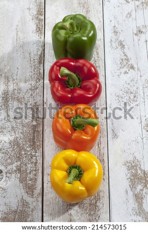Red yellow orange green bell peppers on wooden table, high angle view