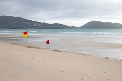 Red yellow warning flag on beach