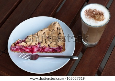 Redcurrant meringue tart on the plate with fork and coffee latte on wooden table