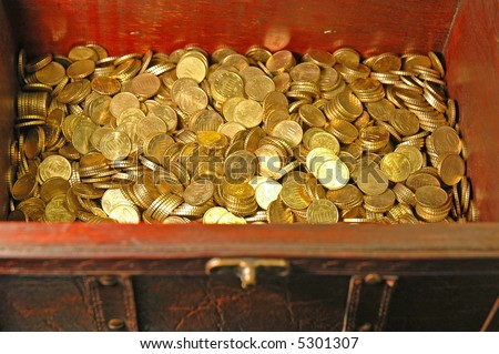 Reddish brown leather and wood treasure chest with gold colored coins (10 euro cent pieces) inside...Focus on the money inside