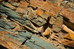 Reddish layered rock wall, with visible geological strata in the