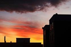 Reddish sunrise and backlit building