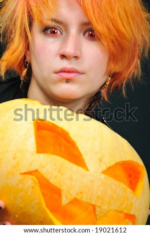 redhair witch with pumkin on black background