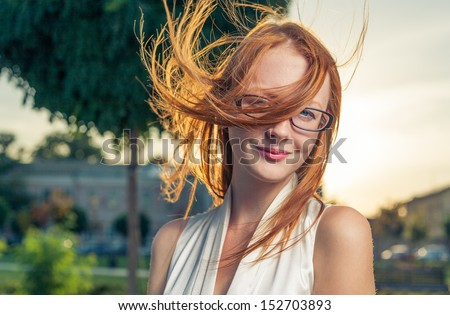 Redhead backlit by the sun. Portrait of cute red haired young woman, outdoors in the park, backlit. Hairs on the wind.
