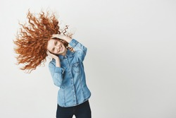 Redhead beautiful girl smiling looking at camera smiling shaking curly hair. White background.