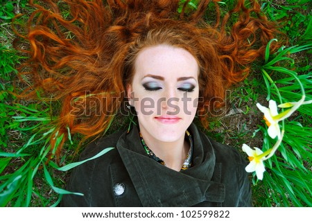 redhead beauty laying on the grass