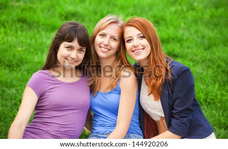Redhead, brunette and blonde girl sitting at green grass in the park.