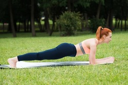 Redhead caucasian girl standing in a plank on a mat on the grass in the park