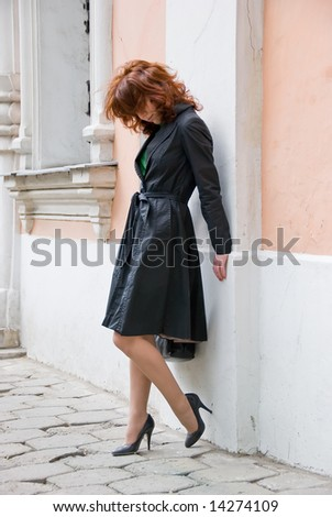 Redhead curly girl stand near an ancient wall