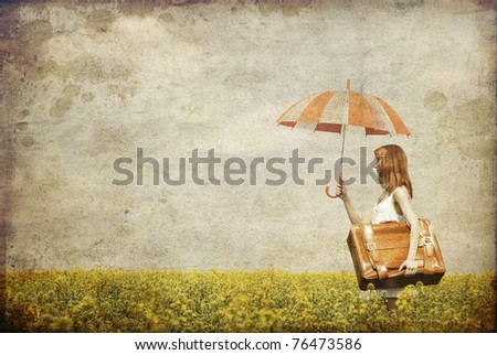Redhead enchantress with umbrella and suitcase at spring rapeseed field. Photo in old image style.
