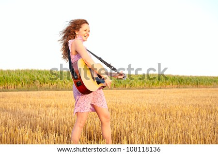 Redhead energetic woman playing guitar outdoors on the field in summer evening