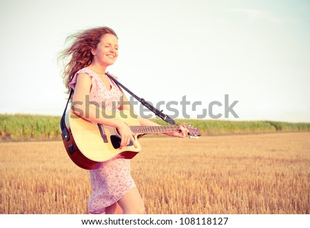 Redhead energetic woman playing guitar outdoors on the field in summer evening. Split toning