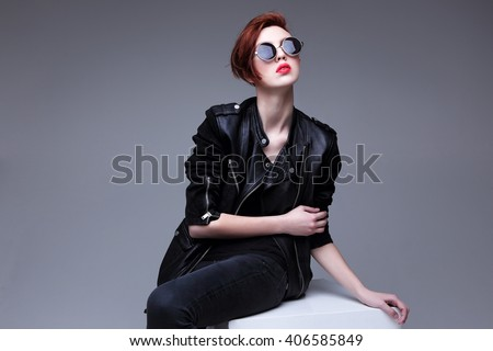 Stock Photo Redhead fashion model in sunglasses and black leather jacket. Pixie cut hairstyle. Punk, rock style fashion