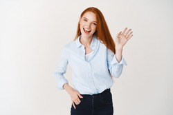 Redhead female hr manager saying hello, waving hand and smiling friendly, greeting you, standing over white background.