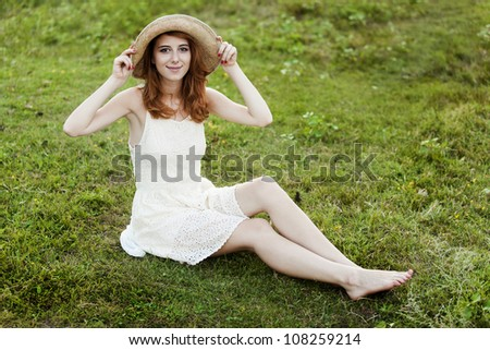 Redhead girl at green grass at village outdoor.