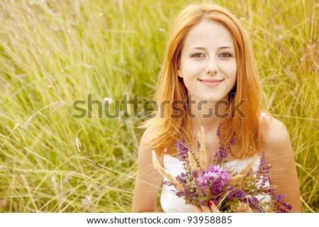 Redhead girl at outdoor with flowers.
