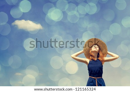 Redhead girl at spring blue sky background. Photo with bokeh at background.