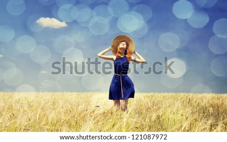 Redhead girl at spring wheat field.  Photo with bokeh at background.