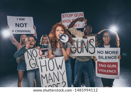 redhead girl holding placard with how many more lettering and screaming in megaphone near multicultural people on black  #1485994112