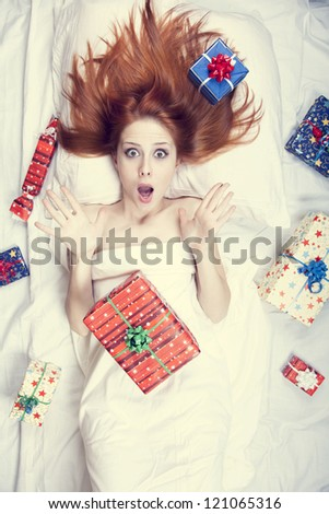 Redhead girl in bed with gifts. Photo in warm tone style.