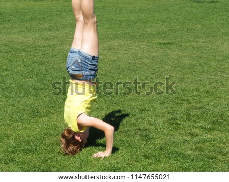 Stock Photo Redhead girl in denim shorts performs a headstand. Yoga outdoors, fitness training, acrobatics on the green grass in summer meadow. Healthy lifestyle concept