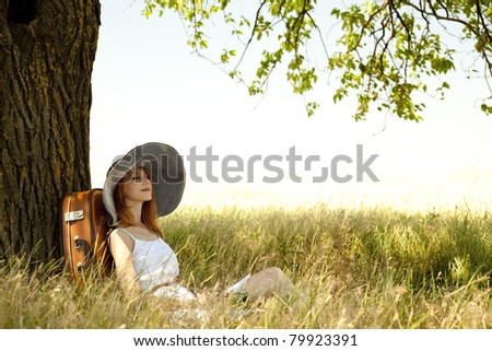 Redhead girl in hat sitting near tree at countryside.