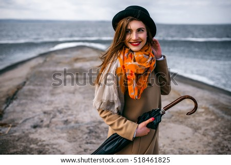 Redhead girl in hat with umbrella by the sea