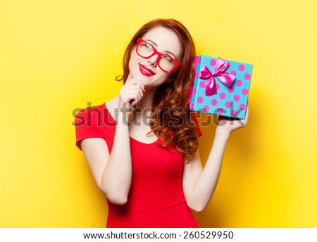 Redhead girl in red dress with glasses and gift box on yellow background