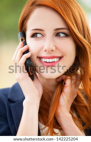 Redhead girl speaking by phone