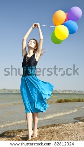 Redhead girl with colour balloons at coast.