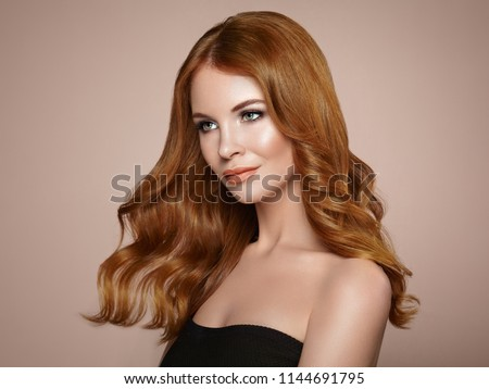 Redhead Girl with Long Healthy and Shiny Curly Hair. Care and Beauty. Beautiful Model Woman with Wavy Hairstyle. Make-Up and Black Dress #1144691795