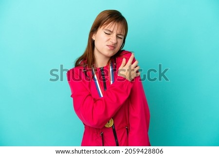 Redhead girl with medals isolated o blue background suffering from pain in shoulder for having made an effort Foto stock ©