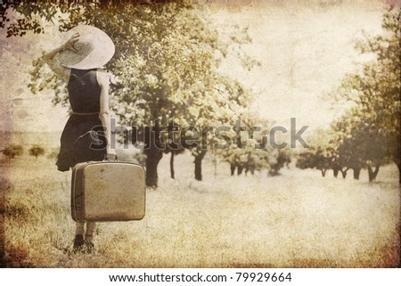 Redhead girl with suitcase at countryside. Photo in old image style.
