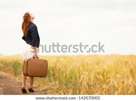 redhead girl with suitcase at...