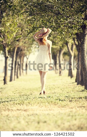 Redhead girl with suitcase at tree's alley. - stock photo
